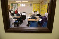 Seventh-grade girls work on an English at the Qalam Collegiate Academy in Richardson. Housed in an office building on West Buckingham Road, a sign stenciled on the door is one of the only outside markers to the school.(Rose Baca - neighborsgo staff photographer)
