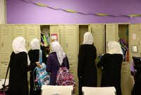Students — dressed in black abaya robes with white scarves over their heads — visit their lockers between class periods. According to a 2010 religious census by the Association of Religious Data Archives, the Muslim population estimate in Dallas County totaled 25 congregations and more than 84,000 adherents.(Rose Baca - neighborsgo staff photographer)