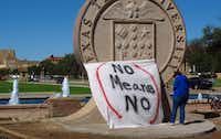"FILE - In this Wednesday, Oct. 1, 2014 file photo, Texas Tech freshman Regan Elder helps drape a bed sheet with the message ""No Means No"" over the university's seal at the Lubbock, Texas campus to protest what students say is a ""rape culture"" on campus. (AP Photo/Betsy Blaney)"