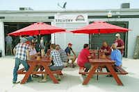 People smoke cigars on the patio of Four Bullets Brewery.(Nathan Hunsinger - Staff Photographer)