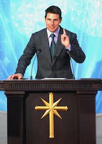 Actor Tom Cruise gestures while making a speech during the official opening of a new Scientology church in central Madrid in this Sept. 18, 2004 file photo.