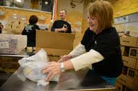 Susan Trussell, a volunteers from Saville, Dodgen and Co., helps pack meals for the Food 4 Kids program, which provides weekend meals to students, at the North Texas Food Bank in Dallas. The meals feed 11,000 students, including students in Rockwall ISD and Rowlett, each weekend.( ROSE BACA )