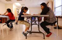 Intern Stephanie Jimenez helps Yanisel Martinez, 8, with her homework during the after-school program at Wesley-Rankin Community Center in West Dallas.(Photos by ROSE BACA)