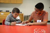 Volunteer Aldo Padilla (right) teaches the alphabet to Daniel Melendez during the Vickery Meadow Summer Reading Academy at Jack Lowe Sr. Elementary School in Dallas. The reading  program was started in 2010 with a group of 16 students, and now has grown to 130 students and about 60 tutors.Staff photos by Rose Baca  - neighborsgo staff photographer