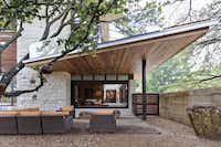 The home is designed around a live oak tree, which stretches through a second-floor balcony.