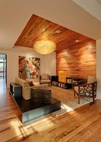 Visual texture, such as the wicker urchin light fixture, and rich rugs add softness to the six-bedroom house.
