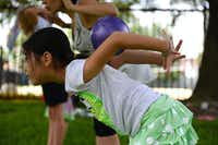 Vika Yun, 8, rolls a ball down her back during summer camp at River of Life.ROSE BACA - neighborsgo staff photographer