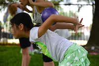 Vika Yun, 8, rolls a ball down her back during summer camp at River of Life.(ROSE BACA - neighborsgo staff photographer)