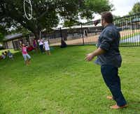 Pastor Leonid Regheta throws a hula hoop to Anya Malamis, 7, during summer camp at River of Life, an evangelical Christian church that caters to Russian-speaking immigrants, which operates out of Hunters Glen Baptist Church in Plano.ROSE BACA  -  neighborsgo staff photographer