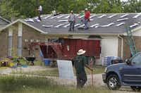 Roofers work on a home on Woodcrest Lane in Lancaster.