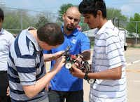 Instructor Jose Guerrero, center, helps team members Bullis and Carlos Lopez repair one of the team's cars during practice.(Photo by RUTH HAESEMEYER - Special Contributor)