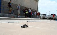 Students watch as R.L. Turner High School junior Seth Bullis (second from left) guides a radio-controlled car around a track as part of Student Racing Challenge class.(Photos by RUTH HAESEMEYER - Special Contributor)