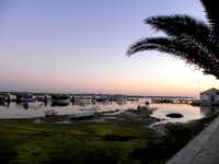 The setting sun glints off the still water of the Ria Formosa lagoon during an April sunset in Santa Luzia, Portugal, as octopus fishing boats run aground with low tide.