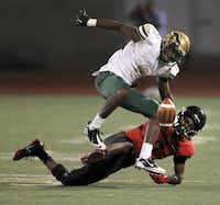 Trinity Trojans defensive back Dany Mulanga (2)  forces a fumble by DeSoto Eagles' WR Akile Davis (8) in the second half of high school football action at Kincaide Stadium Sept. 14. The fumble went out of bounds and stayed with DeSoto.