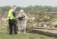Ruth Labenz is assisted to safety by a Stanton County Sherriff's officer after her home was destroyed in the town of Pilger, Neb. Monday, June 16, 2014. At least one person is dead and at least 16 more are in critical condition after two massive tornadoes swept through northeast Nebraska on Monday. (AP Photo/Mark 'Storm' Farnik)(Mark 'Storm' Farnik - AP)