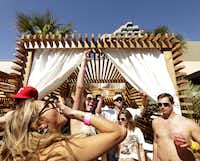 Guests drink and dance by their reserved cabana during a pool party at Sisu in Dallas, TX, on May 5, 2013.