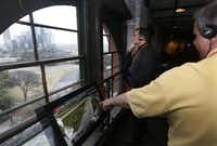 Visitors peer out a window overlooking Dealey Plaza at the Sixth Floor Museum.( Michael Ainsworth  -  Staff Photographer )