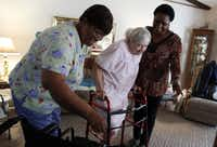 Caregivers Gloria Black, left, and Kandee Smith help Irene Maxa with household needs while Maxa's daughter is at work.