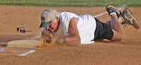 The third baseman for the team playing against the Greyhounds dives to touch third base for a force-out. The Greyhounds, who compete in the North Texas Senior Softball Association, are all ages 70 to 75 and play two games each Monday night at Mike Lewis Park in Grand Prairie.Photos by Louis DeLuca - Staff Photographer