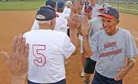 Clyde Benton (right) and Greyhounds teammates high-five the opposing team's players after the game.(Louis DeLuca - Staff Photographer)
