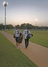 Benton (left) walks to his car while visiting with an opponent after the teams' doubleheader.(Louis DeLuca - Staff Photographer)