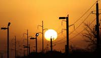 Overhead power lines and light poles owned by Oncor are silhouetted as the morning sun rises over Camp Wisdom Road in Dallas on Sunday, March 20, 2016. (Irwin Thompson/The Dallas Morning News)