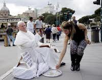 Plisko Julius, a Pope John Paul II impersonator from Slovakia, accepted a tourist's offering after posing for a photo in Rome last week.(Gregorio Borgia - The Associated Press)