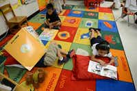 Kindergartners read books in Spanish during class while laying on a mat that displays items with the Spanish and English names for them.Rose Baca - neighborsgo staff photographer