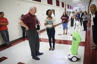 Teacher Vince Rohloff greets student Sara Jones, who returned to school Friday with the aid of a mobile robot for the first time since she had a liver transplant last year. About 100 such robots are in use at K-12 schools around the country.( Matthew Busch  -  Staff Photographer )