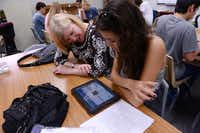 Christina Moreno , 17, and her mother, Robin Rios, wait for Christina's iPad to update during Coppell High School's iPad pick-up day. The free iPads, approved by the district's board, will provide 3,011 students at the school with curriculum and textbooks needed for their education. Read the story on Page 12.
