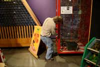 Paul Vinson, director of the Frisco Sci-Tech Discovery Center, a childrenÕs science and technology museum, picks up a loose ball that fell from an exhibit, an exhibit Vinson wishes could be displayed in the center of a room and not in a corner due to lack of space. The city of Frisco recently approved approximately $450,000 worth of renovations to the center as well as its neighbor across the hall, the Frisco Discovery center, home to the Black Box Theatre.