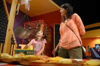 Kate Bittenbender, 6, weighs bread in a scale with her mother Lori at the Frisco Sci-Tech Discovery Center, a childrenÕs science and technology museum. The city of Frisco recently approved approximately $450,000 worth of renovations to the center as well as its neighbor across the hall, the Frisco Discovery center, home to the Black Box Theatre.