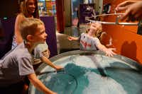 Chase Thomson, 5, reaches out to pop a giant bubble, while Caiden Thomson, 7, and Kelly McKinney look on. The city of Frisco recently approved approximately $450,000 worth of renovations to the Frisco Sci-Tech Discovery Center as well as its neighbor across the hall, the Frisco Discovery center, home to the Black Box Theatre.