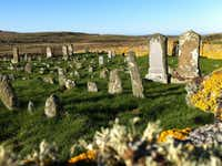 A hiking trail passes alongside a cemetery on the island of Berneray. Some plots appear to be marked by chunks of rock instead of carved headstones.( Cara Anna  -  The Associated Press )