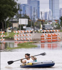Beatrice Banda paddles a boat along a flooded section of Singleton Blvd. at Loop 12 on Saturday, May 30, 2015, in Dallas. (Smiley N. Pool/The Dallas Morning News)