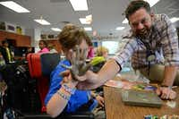 Art teacher Justin Preston helps Kyle Murray, 10, dip his hand into concrete to make his stepping stone in his art class at Anderson Elementary School in Allen.(Rose Baca - neighborsgo staff photographer)