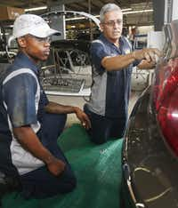 Supervisor Ralph Gonzales  (right) inspects the work of apprentice Kenneth Buford at the shop at 10841 Estate Lane. The chain is a believer in apprenticeships.(2015 File Photo - Staff)