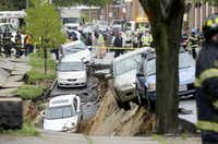 Cars were perched on the edge of a sinkhole Wednesday in the Charles Village neighborhood of Baltimore, as storms began wreaking havoc in the mid-Atlantic region.(The Associated Press)
