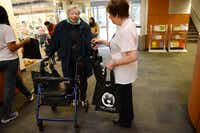 Bev Broman (right) of the Aaron Family Jewish Community Center of Dallas hands a Shabbat in a Bag to Edith Edelbaum.(ROSE BACA)