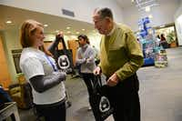 Carmen Finocchio of the Aaron Family Jewish Community Center of Dallas hands a Shabbat in a Bag to Harlan Holiner on Dec. 13. Each bag contained Challah bread a special braided loaf that is part of the Shabbat meal grape juice to represent wine, candles and a Kiddush, a blessing recited over the meal.(ROSE BACA)
