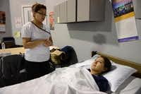 Nayeli Garza Rodriguez performs a skills test on fellow student Rosa Banda Balderes in the nurse aide program.(ROSE BACA)