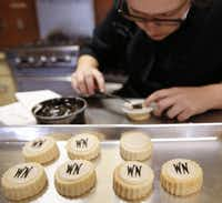 Chef Gillean Williams stencils the Neiman Marcus logo onto shortbread cookies that Le Gourmet Valet owner Becky Nelson developed. Nelson turned down a Trader Joe's deal to pursue Neiman's business.(  Rose Baca  - Staff Photographer)