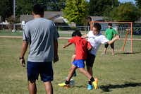 Soccer players Marco Garrido (front) and Jose Marquez struggle for control of the ball during the team's practice at Strickland Intermediate School in Farmers Branch. Aguirre created the team to get students involved in a school activity that would improve their grades and help with behavioral issues.