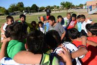 The fourth and fifth grade soccer players get into a huddle during the team's practice at Strickland Intermediate School in Farmers Branch. Aguirre created the team to get students involved in a school activity that would improve their grades and help with behavioral issues.