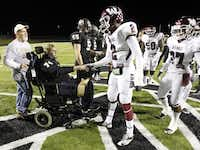Austin, in wheelchair, who was injured in a car accident on Sept. 30, shakes hands with Wylie wide receiver Kameron Kelly (2) as he is escorted by his father Dean Pille prior to the coin flip before the start of the Nov. 8 football game between Wylie High School and Royse City High School in Royse City.Photo by Mike Stone  - Special Contributor