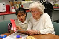 Emeritus at Farmers Branch resident Joan Hinton, 85, helps Maria Jose, 6, a student in Janie Stark Elementary's Two Way Dual Language Program, read in English during a regular after-school tutoring session. The school is known for its community strength and support, in and out of the classroom.(Photo by RUTH HAESEMEYER)