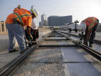 Workers lay track in September 2013 on the Houston Street Viaduct for the downtown-Oak Cliff streetcar project. The line is expected to be up and running by early 2015.(File 2013 - Staff Photo)