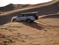 Getting stuck in the sand is half the fun. A second Land Cruiser pulls this guy out from a long fall in the Al Khatim desert two hours out of Abu Dhabi in the United Arab Emirates.