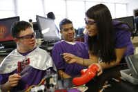 Senior Ivonne Torres, captain of the Sunset robotics team, shows special education students Tomas Sosa (left) and Josh Preciado how to put a battery into a controller. (Rose Baca/Staff Photographer)