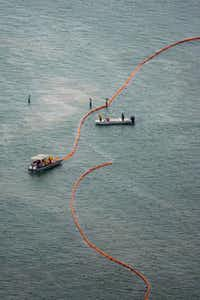 Crews set up protective booms along the seashore near Port Bolivar, part of a cleanup operation that included dozens of ships trying to isolate and remove up to 168,000 gallons of oil spilled into Galveston Bay.(Smiley N. Pool - Houston Chronicle)